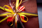 Two foil gifts with yellow,gold,brown bows — Stock Photo