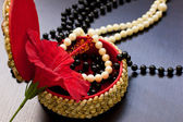 Pearl necklace with red flower on the black table — Stock Photo