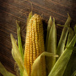 Stock Photo: Ripe corn on dark wooden table with grunge texture