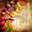 Vintage Autumn border from apples and fallen leaves on old wooden table — Stock Photo #24980997