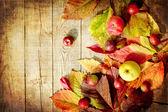 Ročník podzimní hranice z jablek a spadané listí na starý dřevěný stůl — Stock fotografie