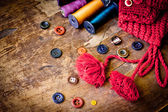 Set of spools of threads vintage buttons with knitted cap on old wooden table — Stock Photo
