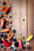 Spools of threads and buttons on old wooden table — Stock Photo