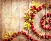 Vintage Autumn border from apples and fallen leaves on old wooden table. — Stock Photo