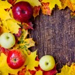 Apples and fallen leaves on old wooden table — Stock Photo #35724307