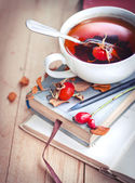 Rosehip tea cup on old books — Stock Photo