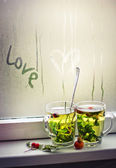 Love inscription on window and two cups — Stock Photo