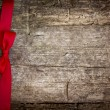 Stock Photo: Red ribbon over wooden background