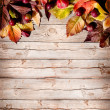 Apples and fallen leaves on old wooden table — Stock Photo