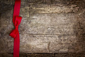 Red ribbon over wooden background — Stock Photo