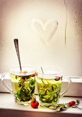 Heart on glass window background and two cups — Stok fotoğraf