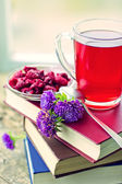 Raspberry hot drink , flowers and books — Stock Photo