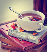 Té de rosa mosqueta sobre libros antiguos — Foto de Stock