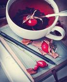 Rosehip tea on old books — Stockfoto