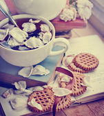Tea with cookies on books — Stock Photo