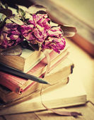 Dry roses on old books — Stock Photo