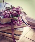 Dry roses on old books — Stok fotoğraf