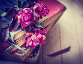 Dry roses on old books — Stockfoto