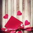 Decorative red ribbon with bow and hearts — Stock Photo