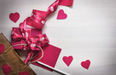 Ribbon, gift, hearts, pencil and paper — Stock Photo