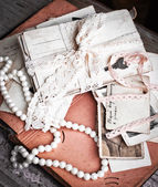 Letters postcards and beads — Stock Photo