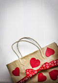 Valentine's gift bag with red ribbon and hearts — Stock Photo