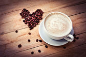 Coffee cup and heart of coffee beans — Stock Photo