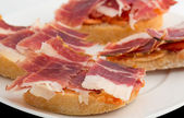 Spanish tapas, ham and tomato — Stock Photo