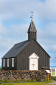 Front view of black wooden church against cloudy sky in Budir, Iceland — Stockfoto