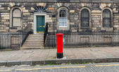 Sidewalk, facades and typical red british postbox — Stock Photo