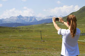 Woman taking a picture of the landscape — Stock Photo