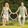 Couple holding heart shaped chalkboard — Stock Photo