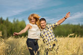 Couple jumping in rye field — Stock Photo
