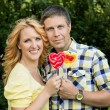 Couple holding heart shaped lollipops — Stock Photo #32180193