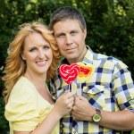 Couple holding heart shaped lollipops — Stock Photo