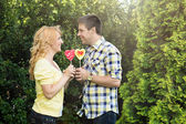Couple holding heart shaped lollipops — Stock Photo
