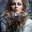 Stock Photo: Girl blowing snowflakes