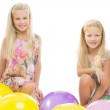Sisters sitting in balloons — Stock Photo