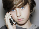 Insightful look blue eyes boy face with telephone — Stock Photo