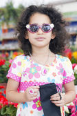 Pretty little girl standing in sunglasses — Stock Photo