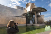Woman taking a picture at the Guggenheim Museum, Bilbao — Stock Photo