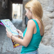 Young female tourist studying a map — 图库照片