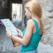 Young female tourist studying a map — Stok fotoğraf