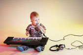 Little boy with microphone and synthesizer — Stock Photo