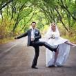 Newly-married couple dancing on the road — Stock Photo