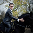 The groom astride on the dark horse - Stock Photo