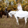 Newly-married couple astride dark and white horses - Stock Photo