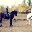 Stock Photo: Newly-married couple astride black and white horses