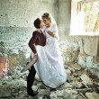 Stock Photo: Newly-married couple kisses in thrown building