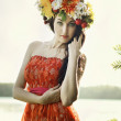 Portrait of Young beautiful woman wearing a wreath of wild flowers — Stock Photo